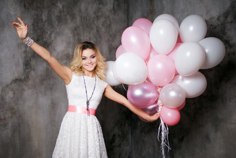 Η γοητεία της νέας ξανθής γυναίκας θέλησε να σας αγκαλιάσει, που κρατάτε μια μεγάλη δέσμη των μπαλονιών στο κόμμα στοκ φωτογραφίες