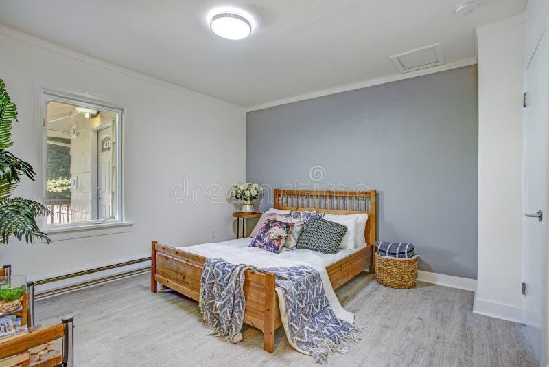 Η γοητευτική κρεβατοκάμαρα χαρακτηρίζει τους άσπρους και γκρίζους τοίχους στοκ εικόνες