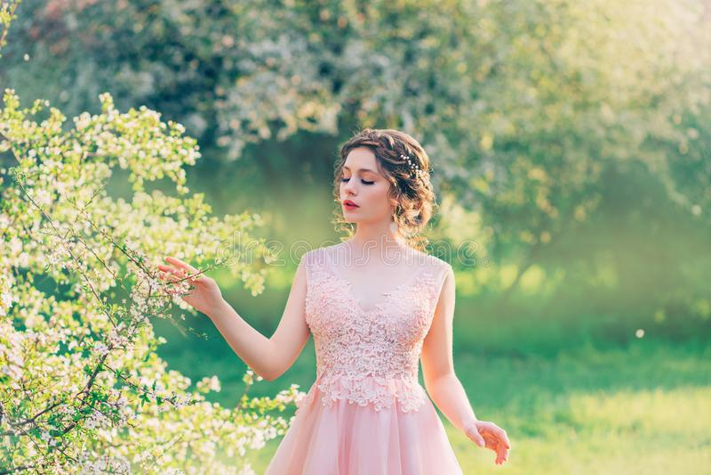 Η γοητευτική κυρία στον ανθίζοντας κήπο, κορίτσι με τη μαζευμένη τρίχα κτυπά ήπια τους κλάδους των δέντρων με τα λουλούδια, κούκλ στοκ εικόνα