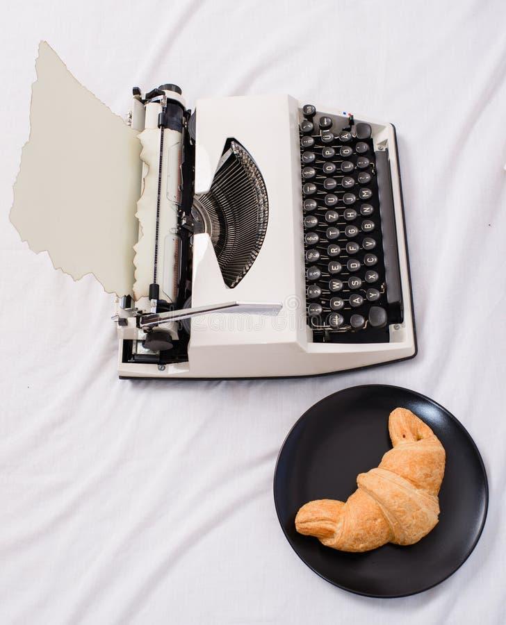 Η γραφομηχανή και το εύγευστο croissant πιάτο βάζουν τα άσπρα σεντόνια Το όφελος που είναι συγγραφέας είναι άνετος εργασιακός χώρ στοκ φωτογραφίες με δικαίωμα ελεύθερης χρήσης