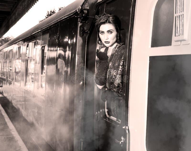 Η γυναίκα έντυσε στο εκλεκτής ποιότητας φόρεμα βραδιού που κλίνει από το παράθυρο τραίνων και που φυσά ένα φιλί στοκ εικόνες