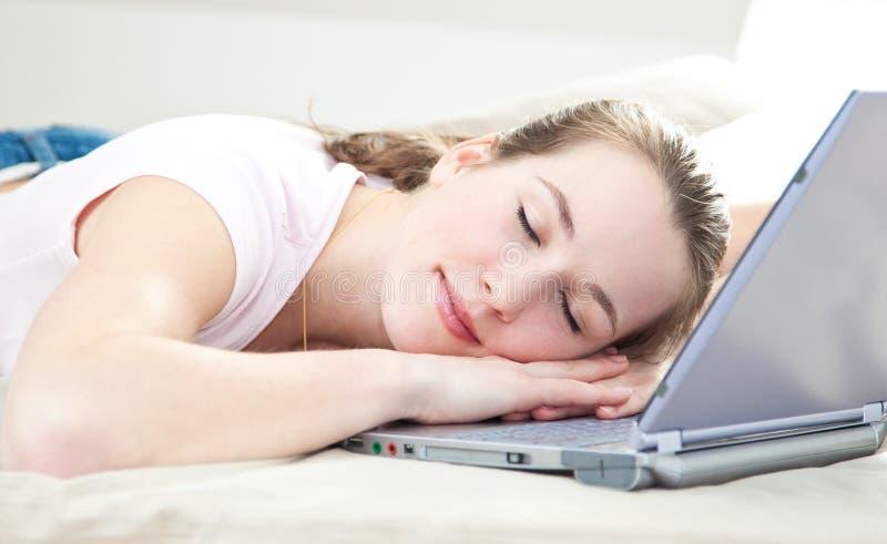 Η γυναίκα έπεσε κοιμισμένη στο lap-top της στοκ εικόνα