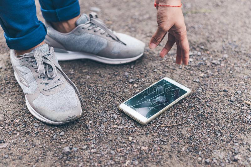 Η γυναίκα έριξε το κινητό τηλέφωνο στο έδαφος και συνέθλιψε την οθόνη στοκ φωτογραφία με δικαίωμα ελεύθερης χρήσης