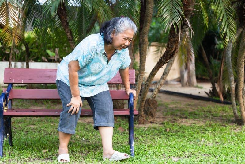Η γυναίκα έχει πόνο στο γόνατο στο πάρκο στοκ εικόνες με δικαίωμα ελεύθερης χρήσης