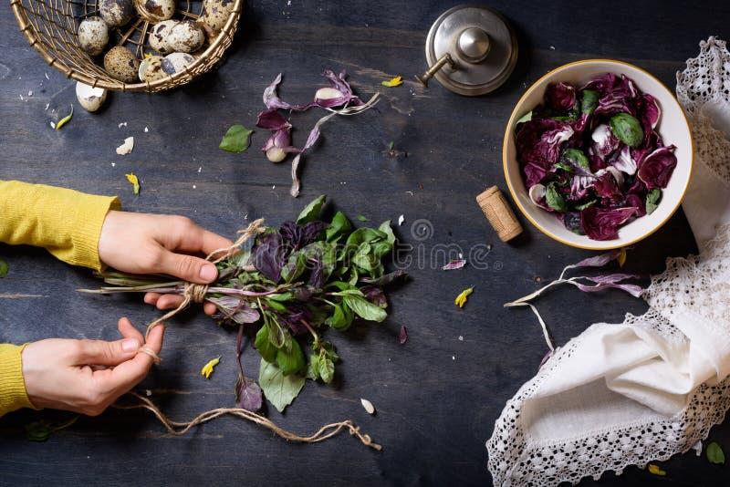 Η γυναίκα δίνει τη μαγειρεύοντας σαλάτα, το φρέσκο βασιλικό, τα φύλλα radicchio και τα αυγά Ξύλινος πίνακας, άμεσα ανωτέρω στοκ εικόνες