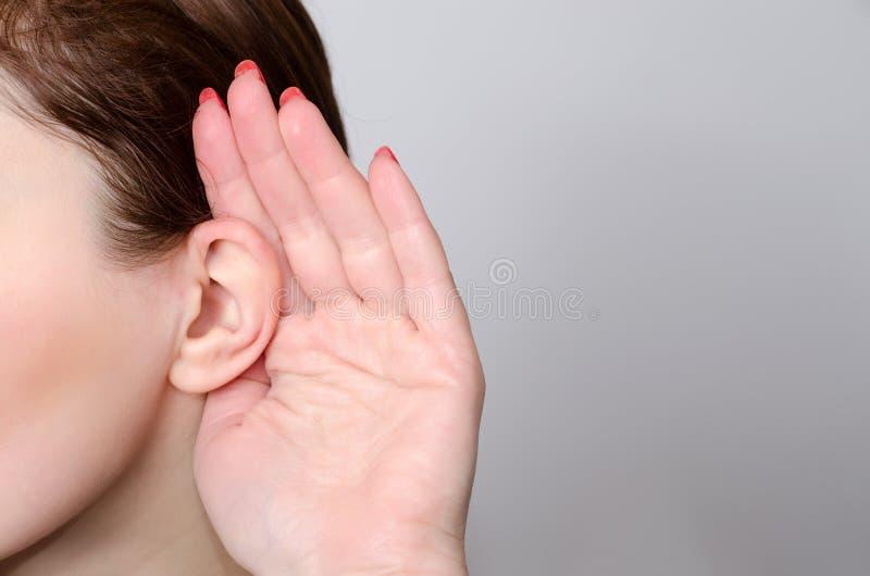 Η γυναίκα ακούει με το χέρι δίπλα στο πρόσωπό της κοντά επάνω στοκ φωτογραφίες με δικαίωμα ελεύθερης χρήσης