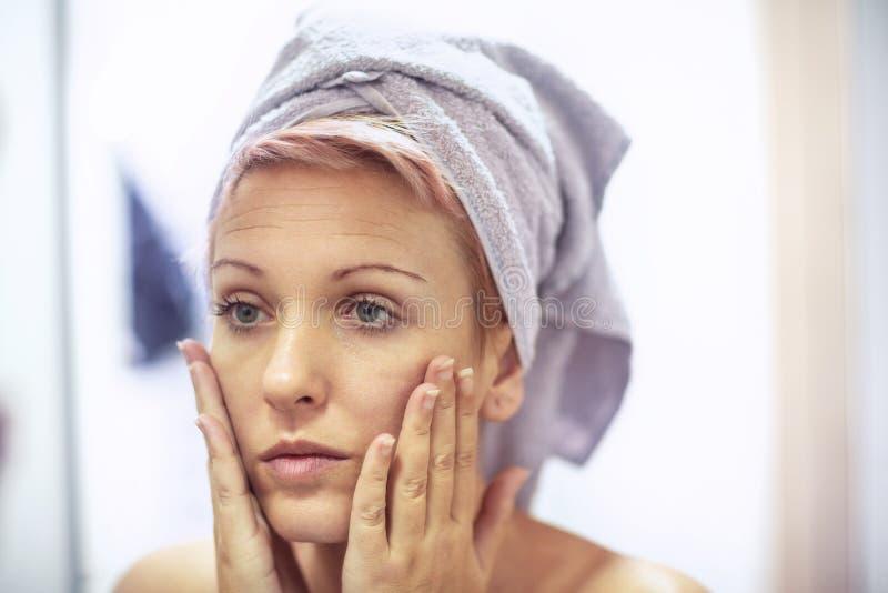Η γυναίκα ανησυχεί για τις ρυτίδες στο πρόσωπό της o στοκ εικόνες