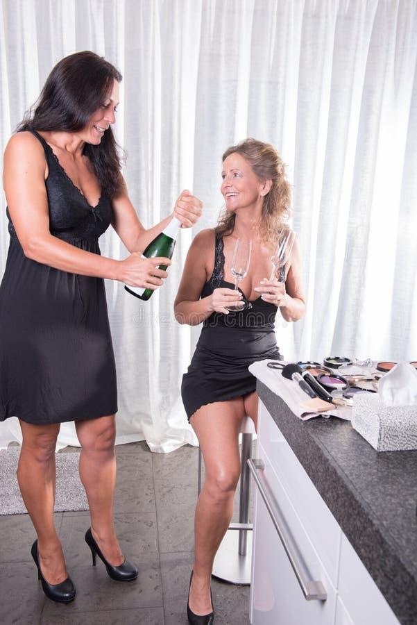 Η γυναίκα ανοίγει ένα μπουκάλι της σαμπάνιας στοκ φωτογραφία με δικαίωμα ελεύθερης χρήσης