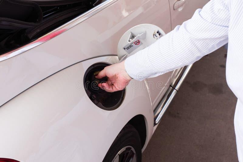Η γυναίκα ανοίγει τη δεξαμενή καυσίμων της ΚΑΠ για να ανεφοδιάσει σε καύσιμα στοκ εικόνες