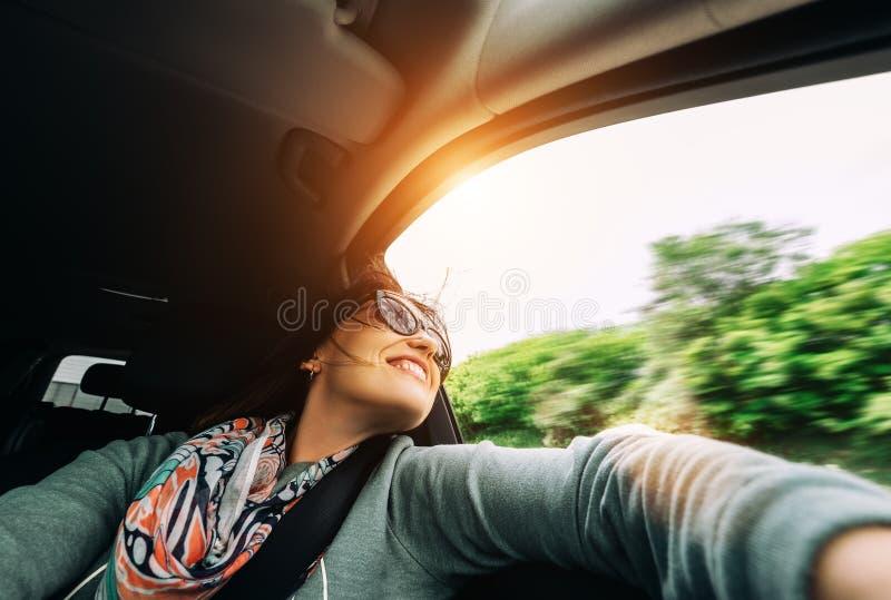 Η γυναίκα απολαμβάνει με την άποψη από το παράθυρο αυτοκινήτων στο ταξίδι με το αυτοκίνητο στοκ φωτογραφίες