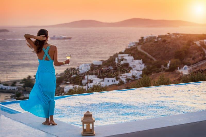 Η γυναίκα απολαμβάνεται ένα ποτήρι του κρασιού από τη λίμνη στη Μύκονο, Ελλάδα στοκ εικόνα με δικαίωμα ελεύθερης χρήσης