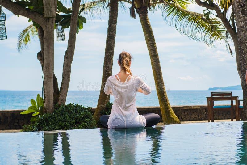 Η γυναίκα από την πλάτη κάθεται στο λωτό θέτει, τεντώνοντας τα χέρια επάνω, που στη λίμνη στην ακτή του ωκεανού στην Ινδονησία στοκ φωτογραφία
