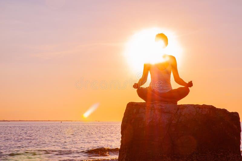 Η γυναίκα ασκεί τη συνεδρίαση γιόγκας στην πέτρα στο Lotus θέτει στο ηλιοβασίλεμα Σκιαγραφία γυναικών στην παραλία στοκ εικόνα