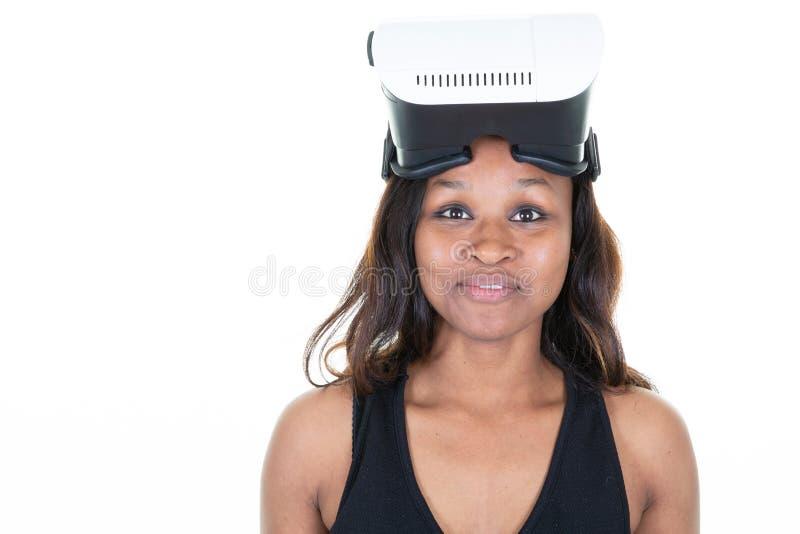Η γυναίκα αφροαμερικάνων αναμιγνύω-φυλών φορά τα προστατευτικά δίοπτρα εικονικής πραγματικότητας που στέκονται στο άσπρο διάστημα στοκ εικόνες