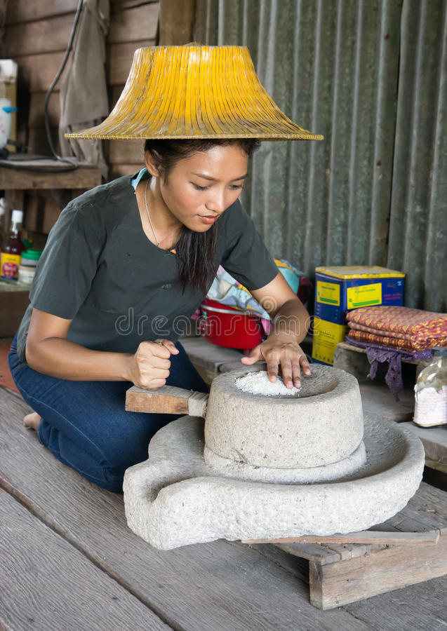 Η γυναίκα αλέθει το ρύζι στο σπίτι της στοκ εικόνες