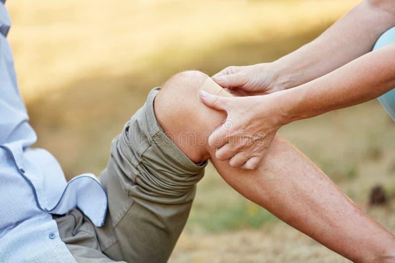Η γυναίκα βάζει μια ενίσχυση ζωνών σε ένα τραυματισμένο γόνατο στοκ φωτογραφία με δικαίωμα ελεύθερης χρήσης