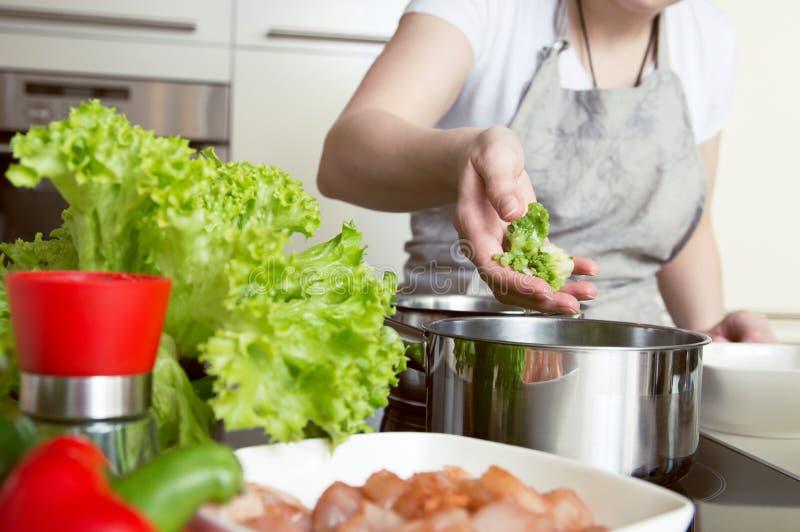 Η γυναίκα βάζει τα λαχανικά στο δοχείο στοκ φωτογραφίες