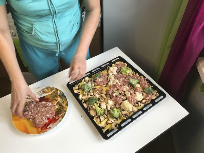 Η γυναίκα βάζει τον κιμά σε ένα φύλλο ψησίματος Σε το ήδη τοποθετημένα τεμαχισμένα μανιτάρια, πατάτες και κουνουπίδι στοκ εικόνα