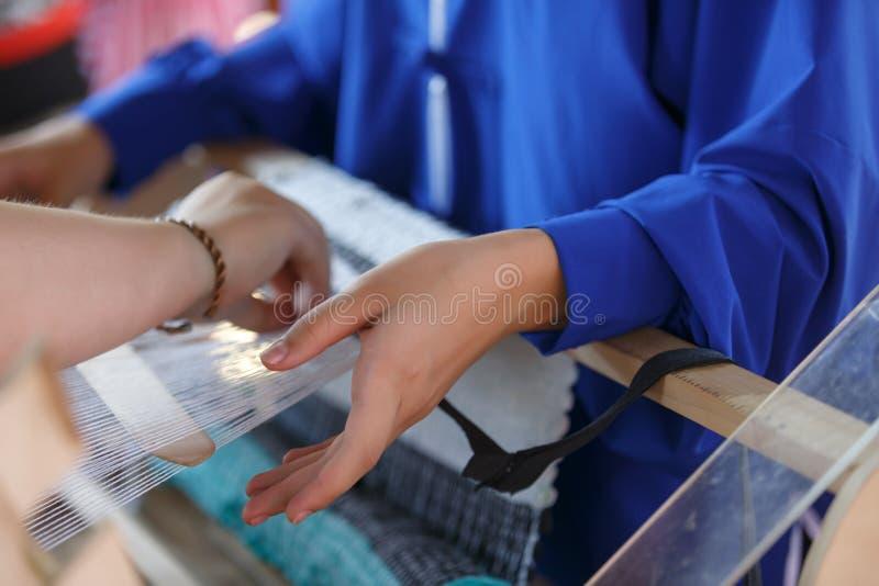 Η γυναίκα βοηθά ένα κορίτσι για να υφάνει το ύφασμα σε έναν αργαλειό r στοκ φωτογραφία