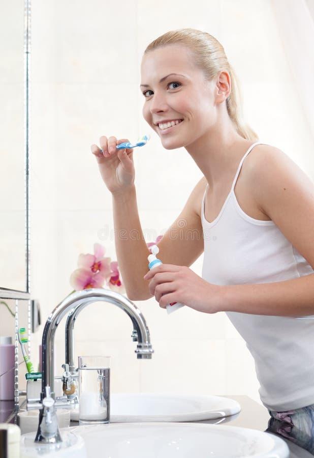 Η γυναίκα βουρτσίζει τα δόντια της για να το κρατήσει άθικτο στοκ φωτογραφία με δικαίωμα ελεύθερης χρήσης