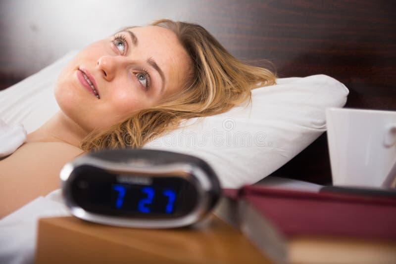 Η γυναίκα βρίσκεται στο κρεβάτι με τα μάτια ανοικτά στην κρεβατοκάμαρα κοντά στο ρολόι και το βιβλίο στοκ εικόνες