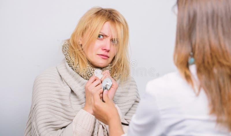 Η γυναίκα γιατρών εξετάζει το άρρωστο πρόσωπο Αναγνωρίστε τα συμπτώματα του κρύου Υπηρεσία εγχώριων επισκεπτόμενη γιατρών E o στοκ εικόνα