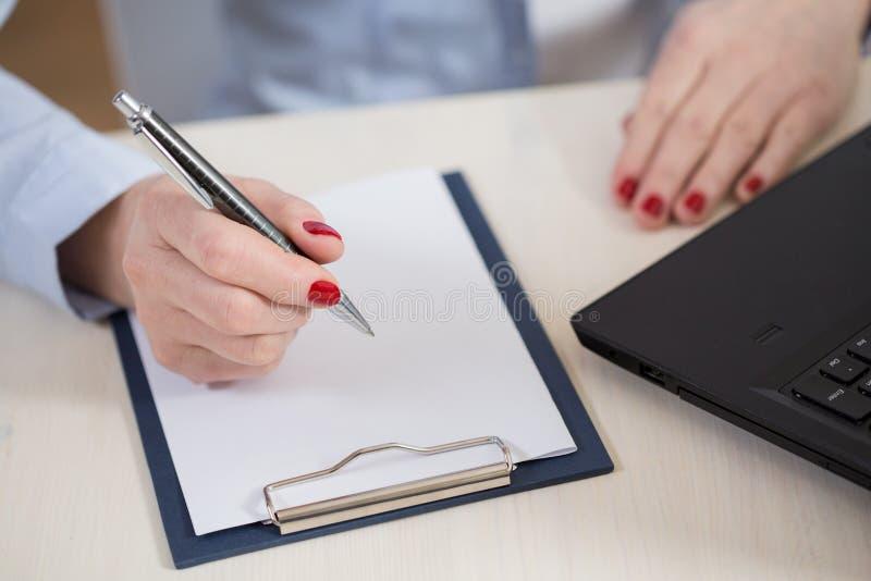 Η γυναίκα γράφει σε ένα σημειωματάριο στοκ εικόνες με δικαίωμα ελεύθερης χρήσης