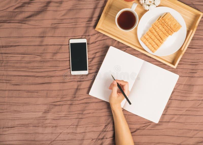 Η γυναίκα γράφει στο μεγάλο άσπρο ανοικτό σημειωματάριο, βάζει στο κρεβάτι με έξυπνο στοκ εικόνες με δικαίωμα ελεύθερης χρήσης