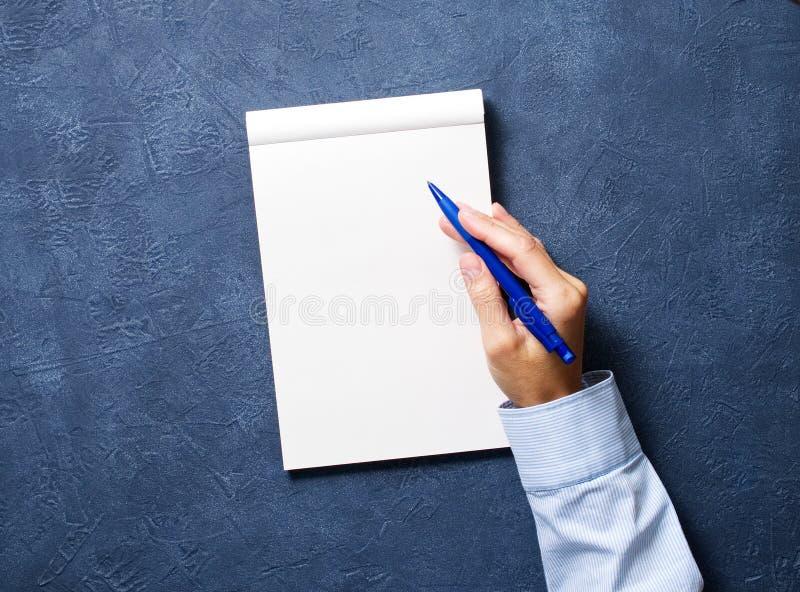 η γυναίκα γράφει στο σημειωματάριο στο σκούρο μπλε πίνακα, παραδίδει το πουκάμισο κρατώντας ένα μολύβι, sketchbook σχέδιο, τοπ άπ στοκ φωτογραφία