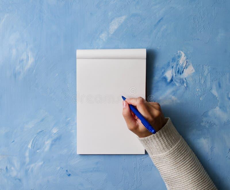 η γυναίκα γράφει στο σημειωματάριο στην πέτρα που ο μπλε πίνακας, παραδίδει το πουκάμισο κρατώντας ένα μολύβι, sketchbook σχέδιο, στοκ εικόνες