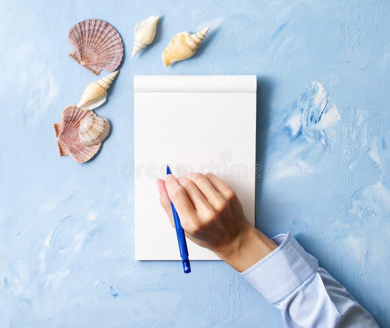 η γυναίκα γράφει στο σημειωματάριο στον μπλε πίνακα πετρών, χλεύη επάνω με το πλαίσιο του θαλασσινού κοχυλιού, τοπ άποψη, που προ στοκ εικόνα με δικαίωμα ελεύθερης χρήσης