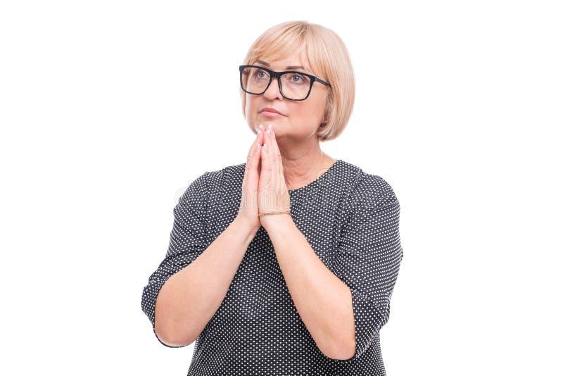 Η γυναίκα δίπλωσε τα χέρια της για την προσευχή και να φανεί ανοδική σε ένα απομονωμένο λευκό υπόβαθρο στοκ εικόνες