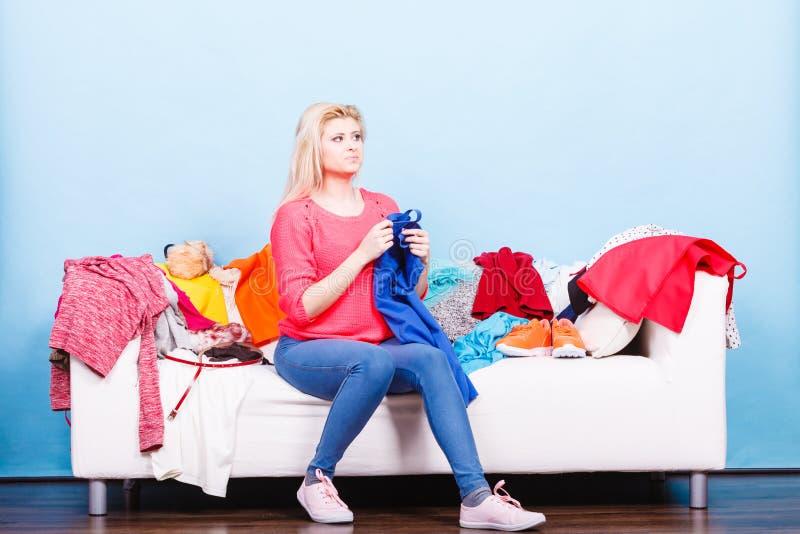 Η γυναίκα δεν ξέρει τι για να φορά τη συνεδρίαση στον καναπέ στοκ εικόνες με δικαίωμα ελεύθερης χρήσης