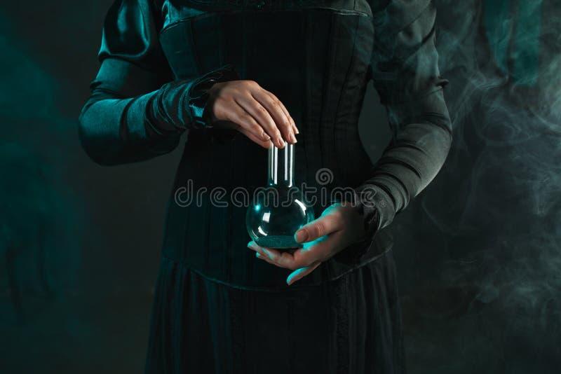 Η γυναίκα είναι ένας ερευνητικός επιστήμονας που κρατά μια φιάλη με το υλικό Έννοια της επιστημονικής έρευνας και της ιστορίας τη στοκ εικόνα