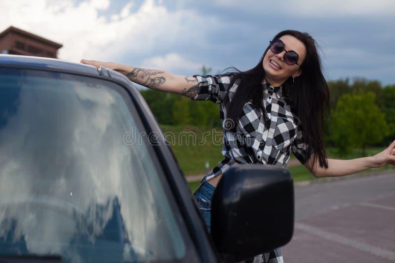 Η γυναίκα είναι κοντά σε ένα αυτοκίνητο στοκ εικόνα