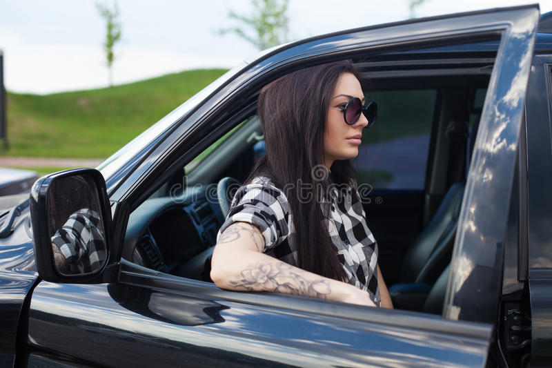 Η γυναίκα είναι κοντά σε ένα αυτοκίνητο στοκ εικόνες