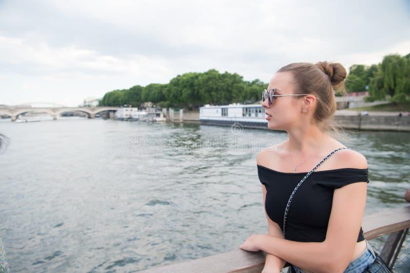 Η γυναίκα εξετάζει τον ποταμό απλαδιών στο Παρίσι, Γαλλία Αισθησιακή γυναίκα στα γυαλιά ηλίου στη γέφυρα τη θερινή ημέρα Διακοπές στοκ εικόνες