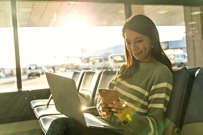 Η γυναίκα εξετάζει το κινητό τηλέφωνο με το lap-top της στον αερολιμένα στοκ εικόνες με δικαίωμα ελεύθερης χρήσης