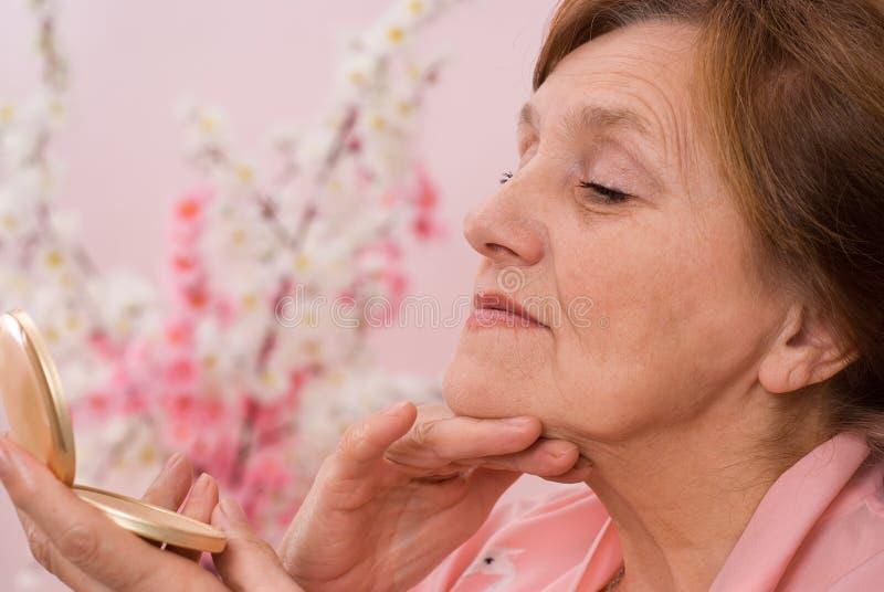 Η γυναίκα εξετάζει το πρόσωπό της στον καθρέφτη στοκ φωτογραφία με δικαίωμα ελεύθερης χρήσης