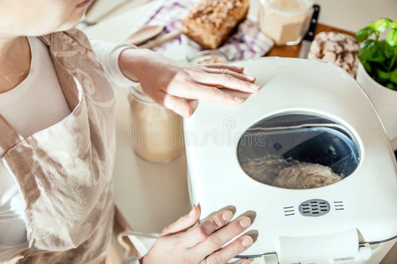 Η γυναίκα εξετάζει το πώς ο κατασκευαστής ψωμιού εργάζεται στοκ εικόνες