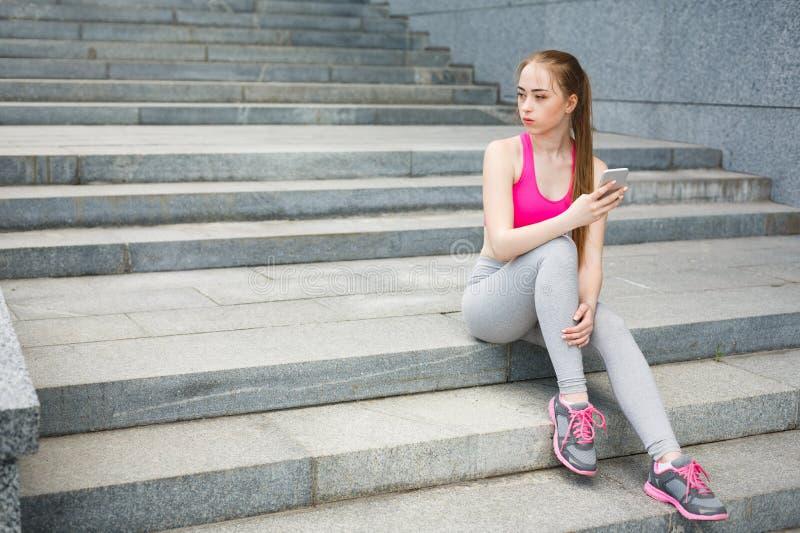 Η γυναίκα επιλέγει τη μουσική για να ακούσει κατά τη διάρκεια του workout στοκ φωτογραφίες με δικαίωμα ελεύθερης χρήσης
