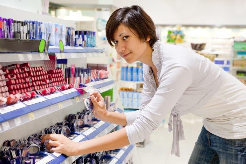 Η γυναίκα επιλέγει το καλλυντικό στο κατάστημα καλλυντικών στοκ εικόνες