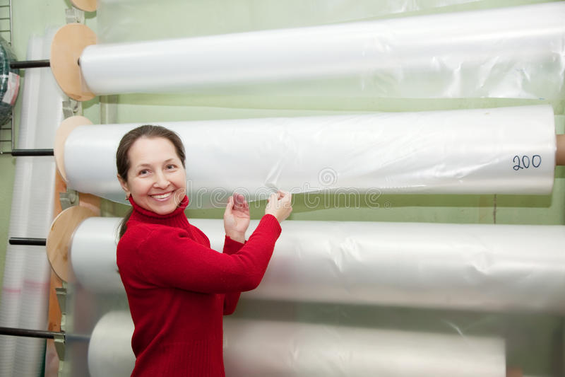 Η γυναίκα επιλέγει το πολυαιθυλένιο για το θερμοκήπιο στοκ εικόνα με δικαίωμα ελεύθερης χρήσης