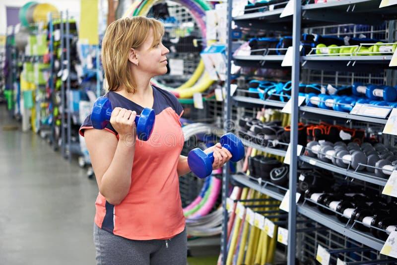 Η γυναίκα επιλέγει τους αλτήρες για την ικανότητα στο αθλητικό κατάστημα στοκ εικόνα
