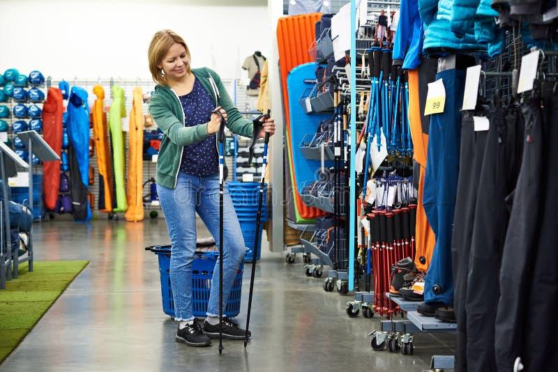 Η γυναίκα επιλέγει τους σκανδιναβικούς πόλους περπατήματος στο κατάστημα στοκ φωτογραφία με δικαίωμα ελεύθερης χρήσης