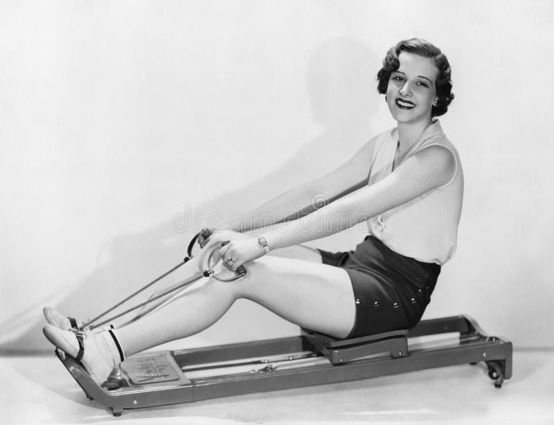 Η γυναίκα επιλύει στη μηχανή κωπηλασίας στοκ εικόνα