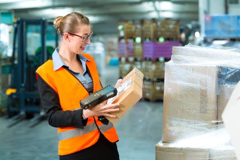 Η γυναίκα εργαζόμενος ανιχνεύει τη συσκευασία στην αποθήκη εμπορευμάτων της αποστολής στοκ εικόνες