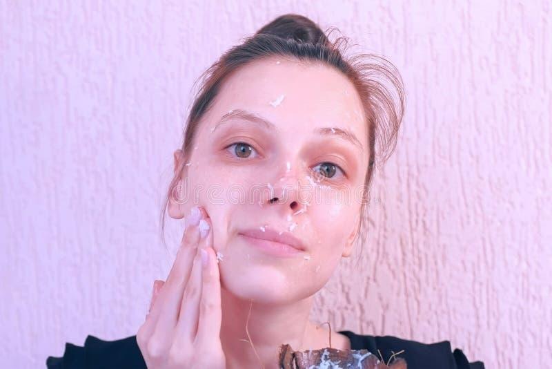 Η γυναίκα εφαρμόζει τη φρέσκια σπιτική καρύδα τρίβει στο πρόσωπο από το κοχύλι καρύδων στοκ φωτογραφία