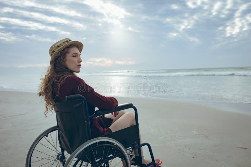 Η γυναίκα θέτει εκτός λειτουργίας τη συνεδρίαση στην αναπηρική καρέκλα στην παραλία στοκ εικόνα