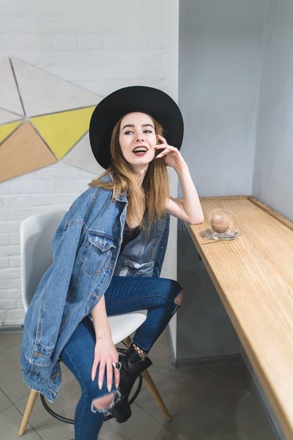 Η γυναίκα θέτει στη κάμερα σε έναν άνετο καφέ για ένα φλυτζάνι του ζεστού ποτού κοντά στο παράθυρο Πορτρέτο ενός κοριτσιού hipste στοκ φωτογραφία